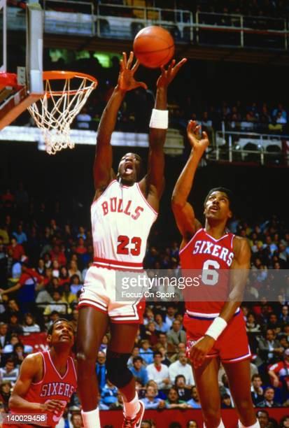 Michael Jordan of the Chicago Bulls pulls down a rebound over Julius Erving of the Philadelphia 76ers during an NBA basketball game circa 1985 at the...