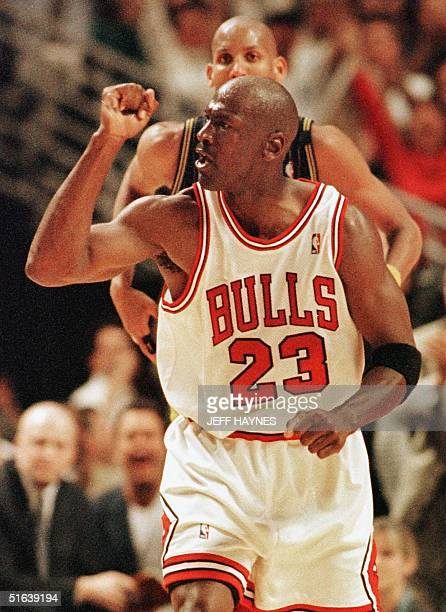 Michael Jordan of the Chicago Bulls pumps his fist after teammate Scottie Pippen made a basket late in the game against Reggie Miller and the Indiana...