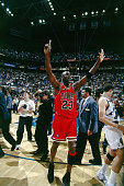 Michael Jordan of the Chicago Bulls raises his hands to signal a 6th championship as he leaves the court after winning the NBA Championpship against...