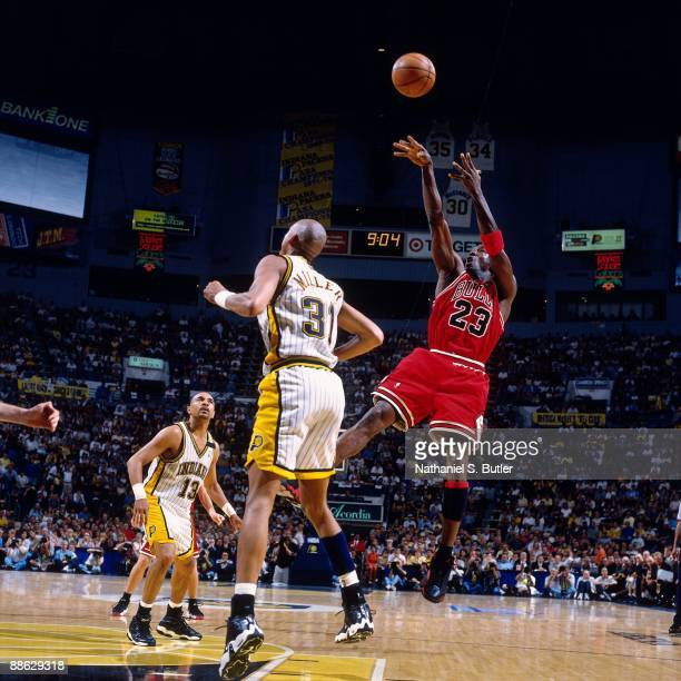 Michael Jordan of the Chicago Bulls shoots a jump shot over Reggie Miller of the Indiana Pacers in Game Six of the Eastern Conference Finals during...