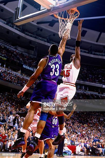Michael Jordan of the Chicago Bulls shoots a layup against Alonzo Mourning of the Charlotte Hornets in Game Three of the Eastern Conference...
