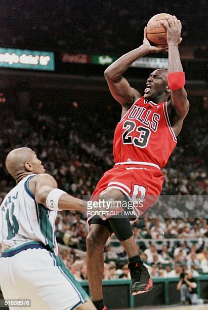 Michael Jordan of the Chicago Bulls shoots over Bobby Phills of the Charlotte Hornets 08 May during game three of their Eastern Conference Semifinal...