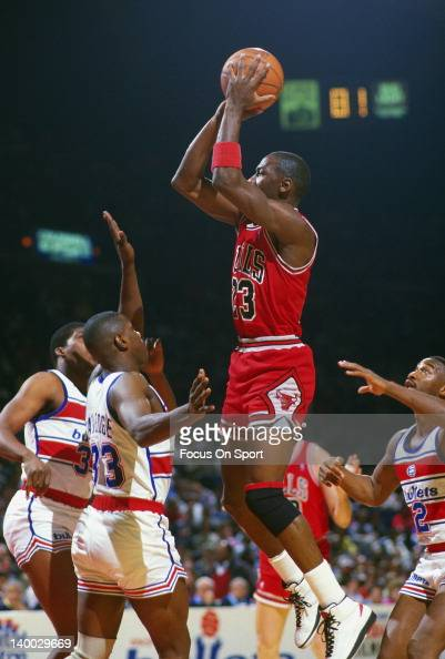 Michael Jordan of the Chicago Bulls shoots over Terry Catledge of the Washington Bullets during an NBA basketball game circa 1986 at the Capital...
