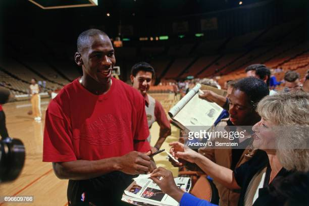 Michael Jordan of the Chicago Bulls signs autographs in a game against the Los Angeles Lakers circa 1985 at the Great Western Forum in Inglewood...