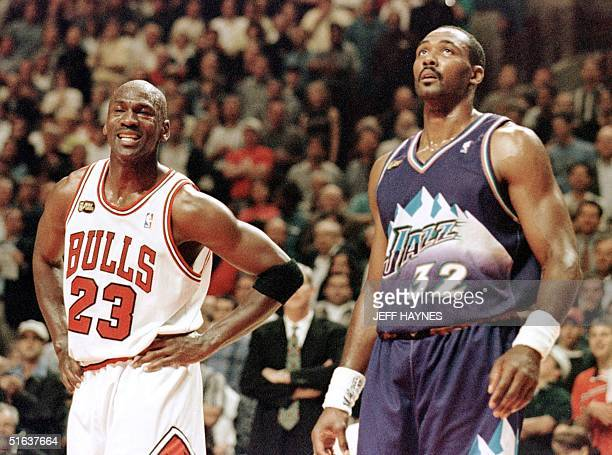 Michael Jordan of the Chicago Bulls smiles while standing next to Karl Malone of the Utah Jazz 07 June in the first half of game three of the NBA...