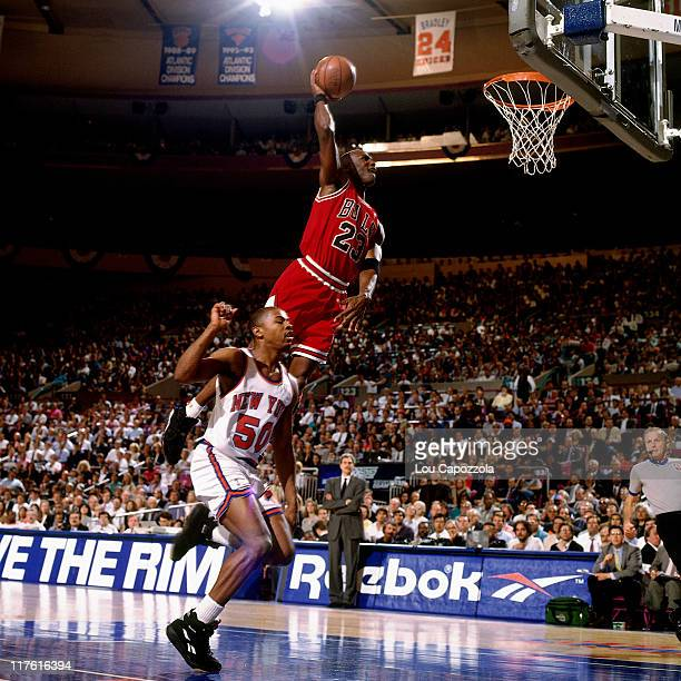 Michael Jordan of the Chicago Bulls soars to the basket for a slam dunk against the New York Knicks during a NBA game circa 1993 at the Madison...