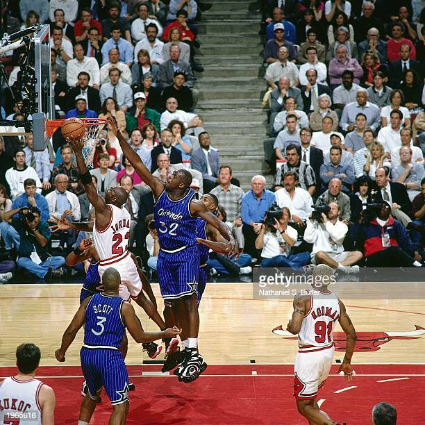 Michael Jordan of the Chicago Bulls takes a layup against Shaquille O'Neal of the Orlando Magic during Game two of the Eastern Conference Finals...