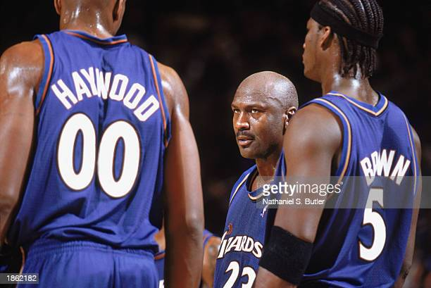 Michael Jordan of the Washington Wizards stands alongside Brendan Haywood and Kwame Brown during the game against the New York Knicks at Madison...