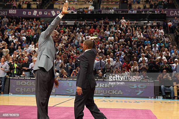 Michael Jordan Owner of the Charlotte Bobcats high fives former Charlotte Hornet Muggsy Bogues before he unveils the new Charlotte Hornets logo...