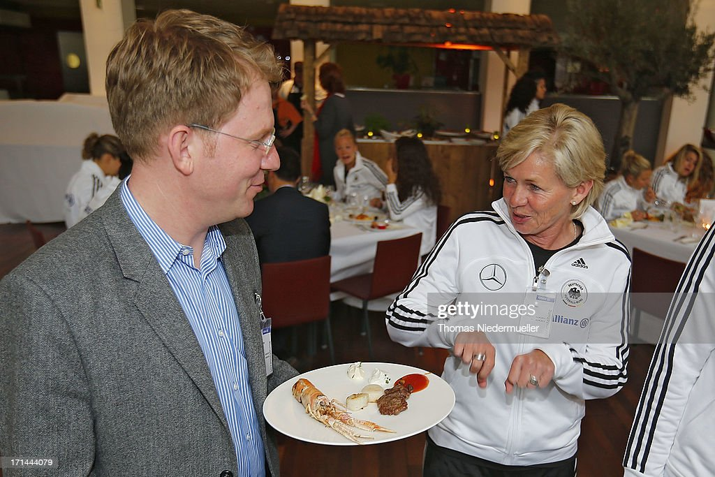 Michael Kaefer and head coach <a gi-track='captionPersonalityLinkClicked' href=/galleries/search?phrase=Silvia+Neid&family=editorial&specificpeople=641230 ng-click='$event.stopPropagation()'>Silvia Neid</a> are seen during the DFB Team & Sponsors Cooking Event on June 24, 2013 in Munich, Germany.