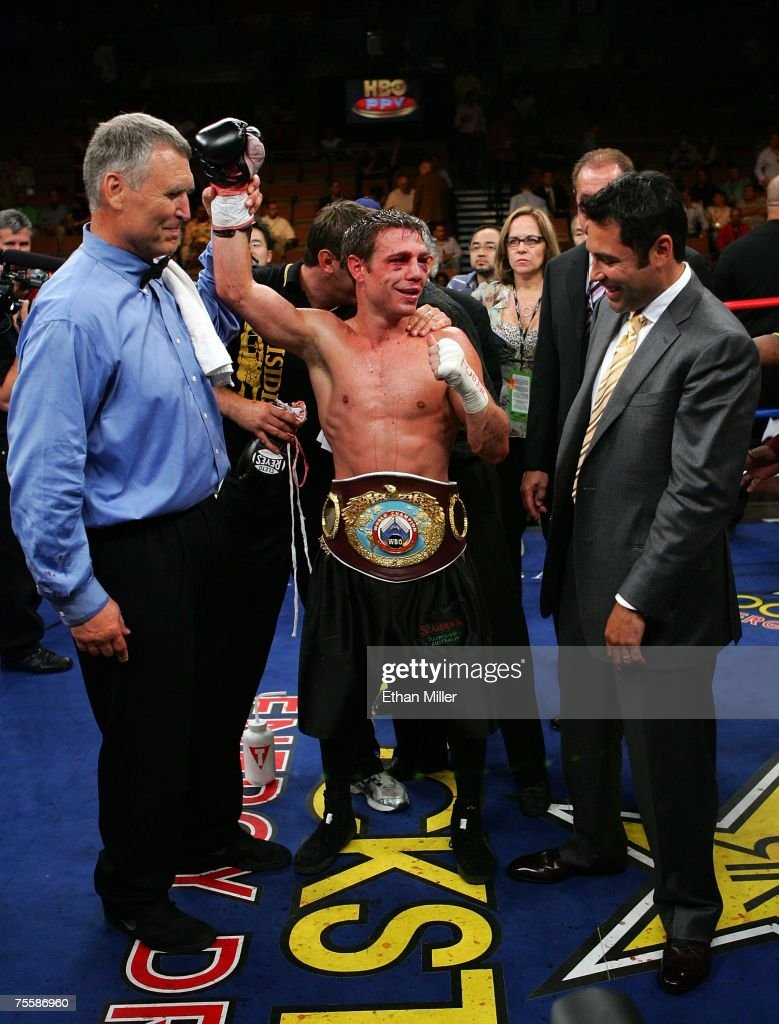 Michael Katsidis of Australia celebrates his unanimousdecision victory as referee Jay Nady holds up his arm and promoter/fighter Oscar De La Hoya...