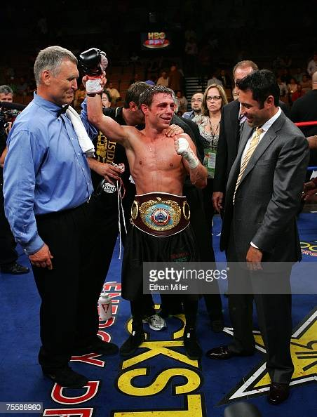 Michael Katsidis of Australia celebrates his unanimousdecision victory as referee Jay Nady holds up his arm and promoter/fighter Oscar De La Hoya...