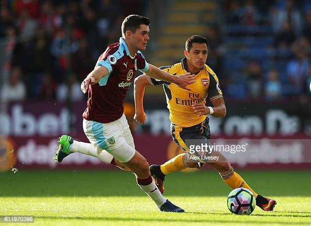 Michael Keane of Burnley and Alexis Sanchez of Arsenal both chase the ball during the Premier League match between Burnley and Arsenal at Turf Moor...