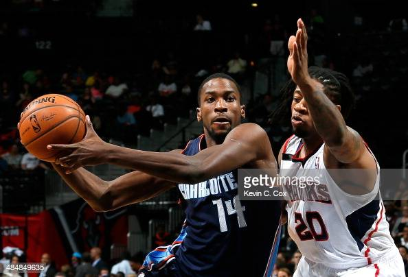 Michael KiddGilchrist of the Charlotte Bobcats drives against Cartier Martin of the Atlanta Hawks at Philips Arena on April 14 2014 in Atlanta...