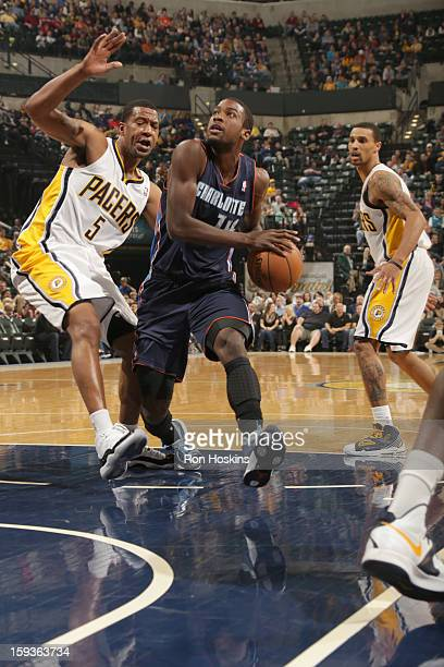 Michael KiddGilchrist of the Charlotte Bobcats drives against Dominic McGuire of the Indiana Pacers during the game between the Indiana Pacers and...