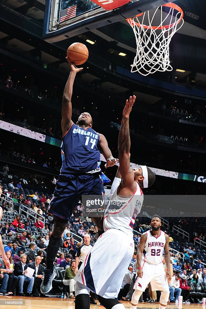 <a gi-track='captionPersonalityLinkClicked' href=/galleries/search?phrase=Michael+Kidd-Gilchrist&family=editorial&specificpeople=8526214 ng-click='$event.stopPropagation()'>Michael Kidd-Gilchrist</a> #14 of the Charlotte Bobcats drives to the basket against <a gi-track='captionPersonalityLinkClicked' href=/galleries/search?phrase=Josh+Smith+-+Basketspelare+-+F%C3%B6dd+1985&family=editorial&specificpeople=201983 ng-click='$event.stopPropagation()'>Josh Smith</a> #5 of the Atlanta Hawks at Philips Arena on December 13 ,2012 in Atlanta, Georgia.
