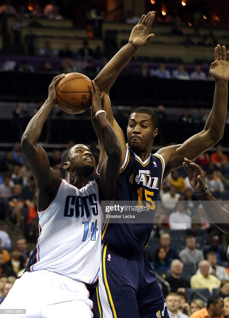 Michael Kidd-Gilchrist #14 of the Charlotte Bobcats drives to the basket against Derrick Favors #15 of the Utah Jazz during their game at Time Warner Cable Arena on January 9, 2013 in Charlotte, North Carolina.
