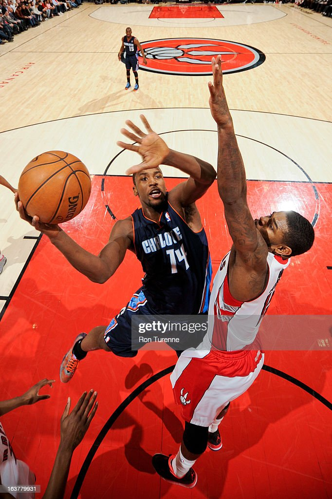 Michael Kidd-Gilchrist #14 of the Charlotte Bobcats drives to the basket against Amir Johnson #15 of the Toronto Raptors on March 15, 2013 at the Air Canada Centre in Toronto, Ontario, Canada.