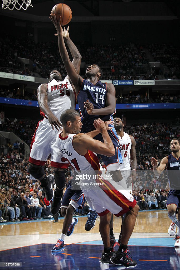 Michael Kidd-Gilchrist #14 of the Charlotte Bobcats goes to the basket against Joel Anthony #50 and Shane Battier #31 of the Miami Heat during the game between the Miami Heat and the Charlotte Bobcats at the Time Warner Cable Arena on December 26, 2012 in Charlotte, North Carolina.