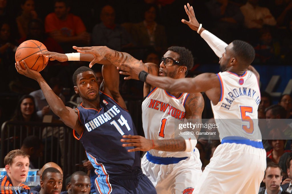 Michael Kidd-Gilchrist #14 of the Charlotte Bobcats looks to pass against Amar'e Stoudemire #1 and Tim Hardaway Jr. #5 of the New York Knicks during the game on November 5, 2013 at Madison Square Garden in New York City, New York.
