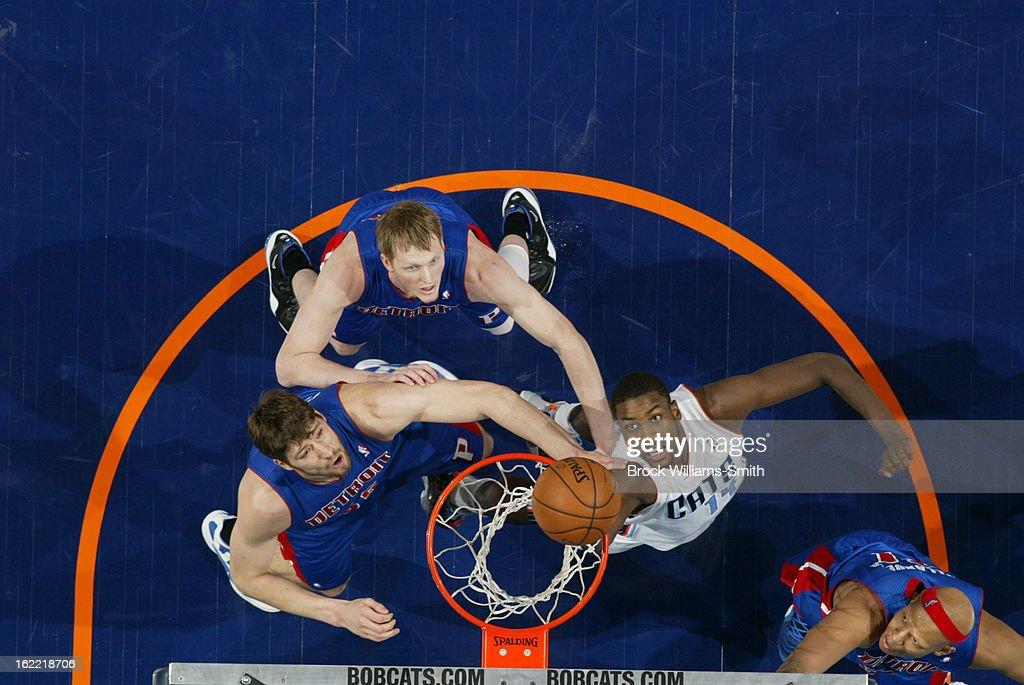 Michael KiddGilchrist of the Charlotte Bobcats shoots against Viacheslav Kravtsov and Kyle Singler of the Detroit Pistons at the Time Warner Cable...