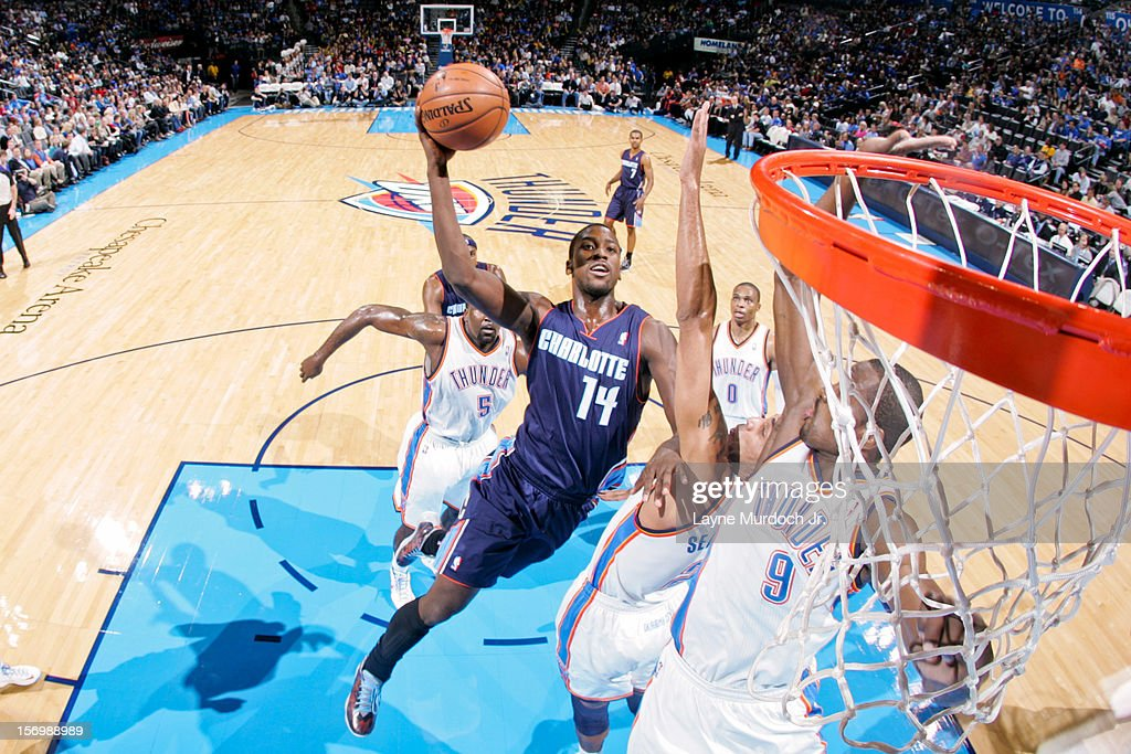 <a gi-track='captionPersonalityLinkClicked' href=/galleries/search?phrase=Michael+Kidd-Gilchrist&family=editorial&specificpeople=8526214 ng-click='$event.stopPropagation()'>Michael Kidd-Gilchrist</a> #14 of the Charlotte Bobcats shoots in the lane against <a gi-track='captionPersonalityLinkClicked' href=/galleries/search?phrase=Thabo+Sefolosha&family=editorial&specificpeople=587449 ng-click='$event.stopPropagation()'>Thabo Sefolosha</a> #2 and <a gi-track='captionPersonalityLinkClicked' href=/galleries/search?phrase=Serge+Ibaka&family=editorial&specificpeople=5133378 ng-click='$event.stopPropagation()'>Serge Ibaka</a> #9 of the Oklahoma City Thunder on November 26, 2012 at the Chesapeake Energy Arena in Oklahoma City, Oklahoma.