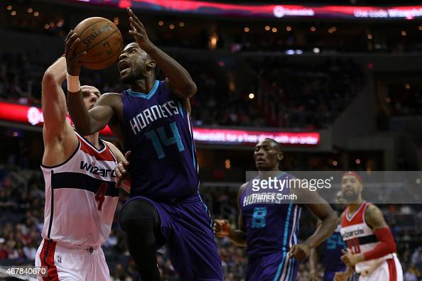 Michael KiddGilchrist of the Charlotte Hornets drives to the hoop as he is defended by Marcin Gortat of the Washington Wizards in the first half at...