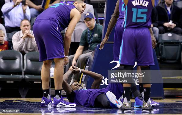 Michael KiddGilchrist of the Charlotte Hornets grimaces as he lies on the floor after being injured during the game against the Indiana Pacers at...