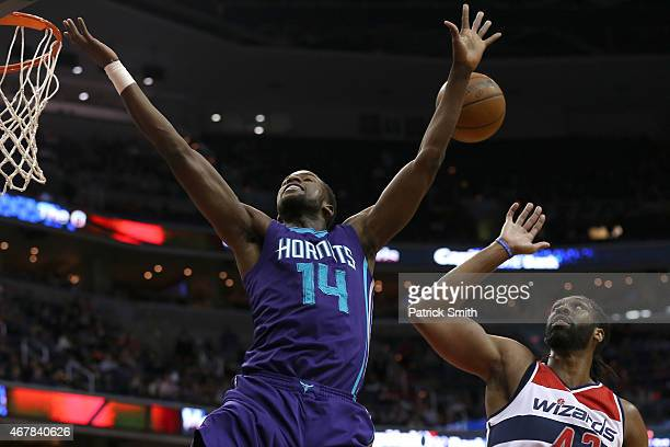 Michael KiddGilchrist of the Charlotte Hornets loses control of the ball as Nene of the Washington Wizards defends in the first half at Verizon...