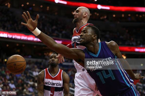 Michael KiddGilchrist of the Charlotte Hornets loses control of the ball as he is defended by Marcin Gortat of the Washington Wizards in the first...