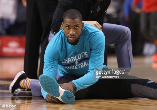 Michael KiddGilchrist of the Charlotte Hornets stretches with the help of a trainer before their game against the Toronto Raptors during NBA game...