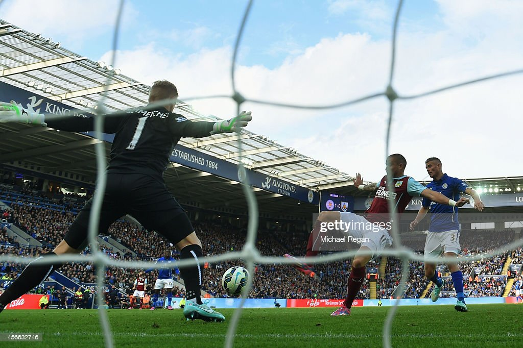 Michael Kightly of Burnley shoots past Kasper Schmeichel of Leicester City to scores their first goal during the Barclays Premier League match...
