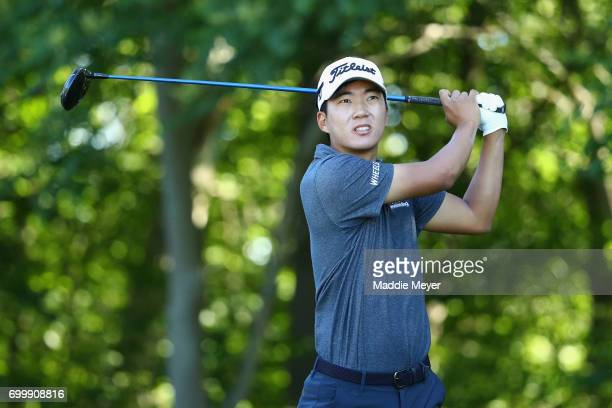 Michael Kim of the United States plays his shot from the 12th tee during the first round of the Travelers Championship at TPC River Highlands on June...