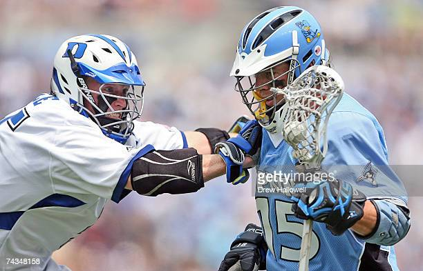 Michael Kimmel of Johns Hopkins gets checked by Parker McKee of Duke on May 28 2007 at MT Bank Stadium in Baltimore Maryland Johns Hopkins University...
