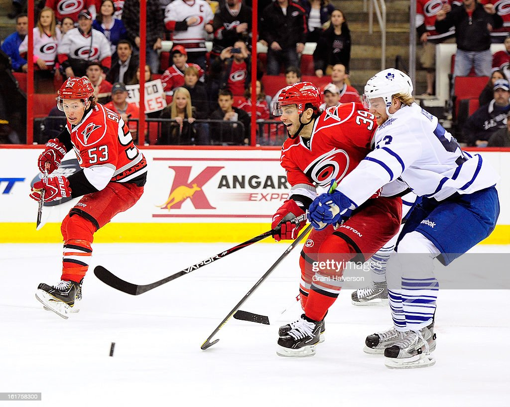 Michael Kostka #53 of the Toronto Maple Leafs and Patrick Dwyer #39 of the Carolina Hurricanes during play at PNC Arena on February 14, 2013 in Raleigh, North Carolina. Carolina defeated Toronto 3-1.