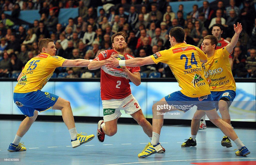 Michael Kraus of Hamburg is challenged by Vid Poteko and Nemanja Zeleovic of Celje during the hanball Champions League game between HSV Hamburg and...