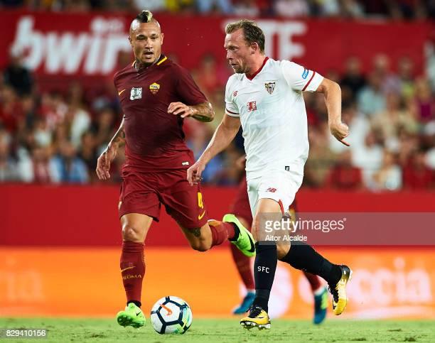 Michael KrohnDehli of Sevilla FC being followed by Radja Nainggolan during a Pre Season Friendly match between Sevilla FC and AS Roma at Estadio...