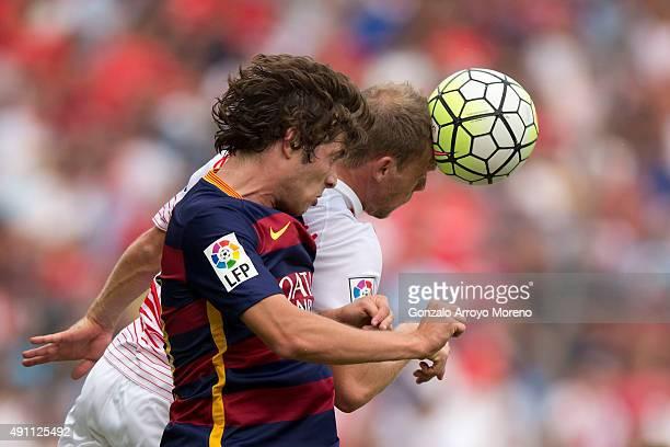 Michael KrohnDehli of Sevilla FC wins the header before Sergi Roberto of FC Barcelona during the La Liga match between Sevilla FC and FC Barcelona at...