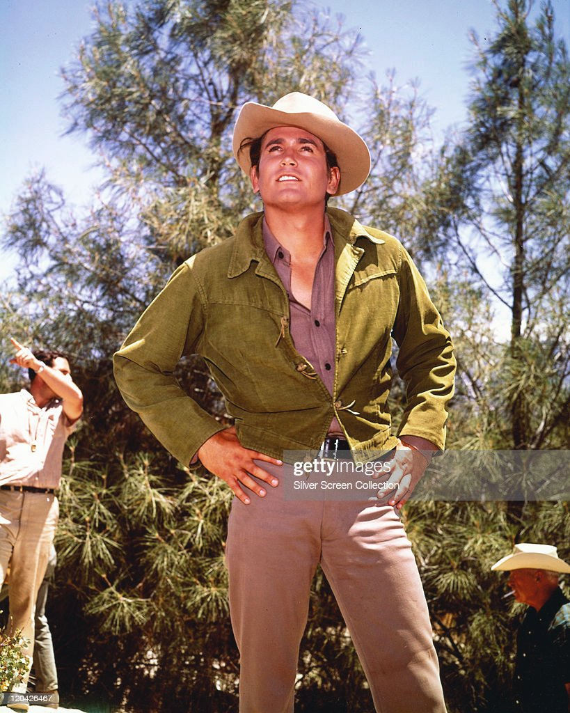 <a gi-track='captionPersonalityLinkClicked' href=/galleries/search?phrase=Michael+Landon&family=editorial&specificpeople=228407 ng-click='$event.stopPropagation()'>Michael Landon</a> (1936-1991), US actor, wearing a cowboy hat and a green jacket on the set of the US television series, 'Bonanza', with the figures of two men in the background, USA, circa 1960. The western series starred Landon as 'Joseph 'Little Joe' Cartwright'.