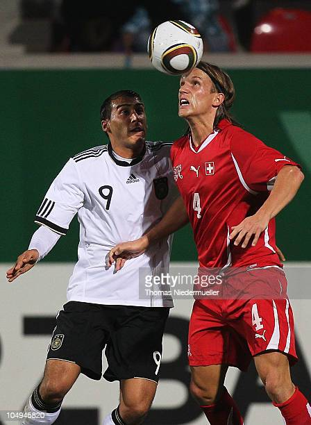 Michael Lang of the Switzerland jumps for a header with Cenk Tosun of Germany during the men's U20 International friendly match between Germany and...