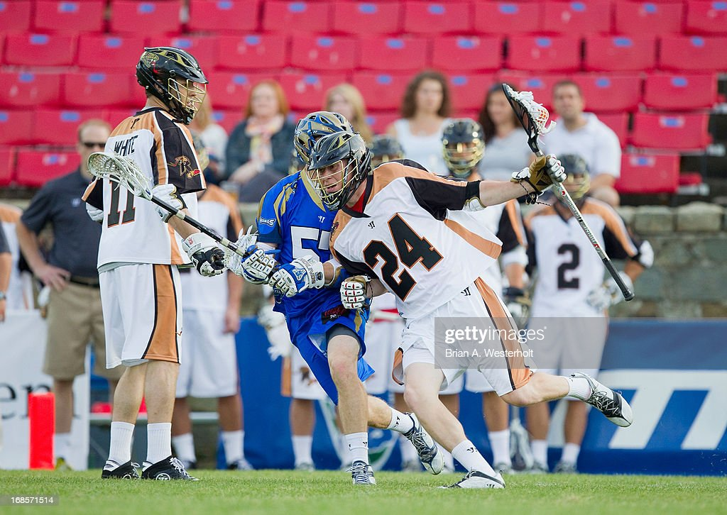 Michael Lazore #24 of the Rochester Rattlers fights off a check from Peet Poillon #57 of the Charlotte Hounds during first half action at American Legion Memorial Stadium on May 11, 2013 in Charlotte, North Carolina.