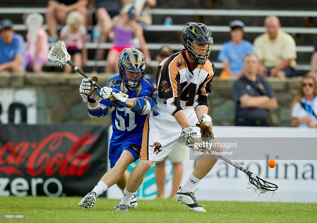 Michael Lazore #24 of the Rochester Rattlers picks up a ground ball in front of Peet Poillon #57 of the Charlotte Hounds at American Legion Memorial Stadium on May 11, 2013 in Charlotte, North Carolina. The Rattlers defeated the Hounds 13-10.