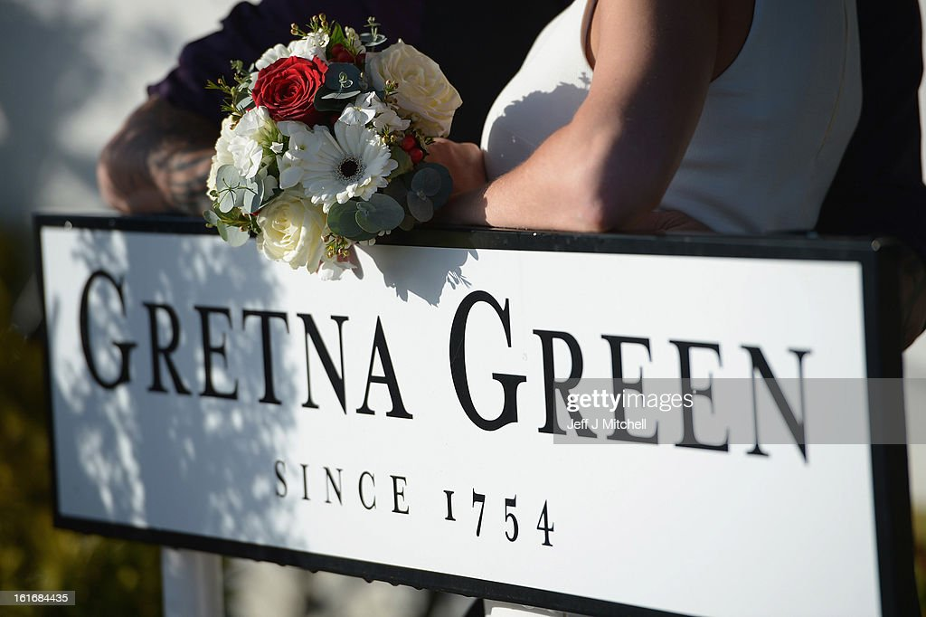 Michael Lewis and Rebecca Anderson pose outside the Gretna Green Famous Blacksmiths Shop on the day of their wedding on Valentine's day on February 14, 2013 in Gretna,Scotland. Gretna Green is one of the most popular wedding destinations in Scotland hosting thousands of weddings each year with a particular rise on St Valentine's Day. Gretna Green has been hosting marriages in the blacksmiths shop since 1754.