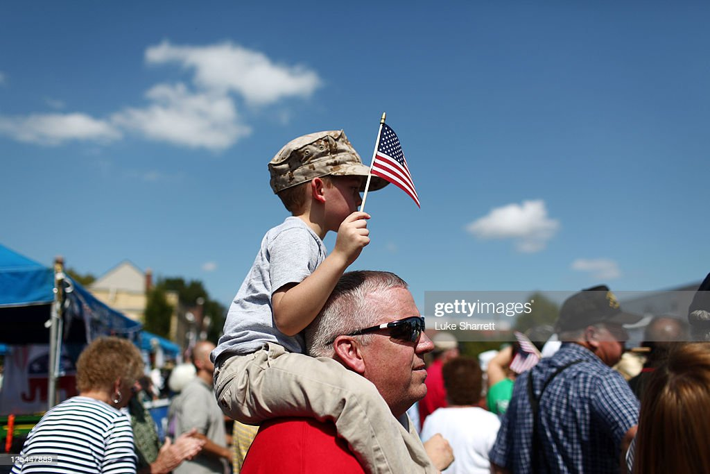 Michael Lewis of Winchester Kentucky sits on his father Thomas Lewis' shoulders with an American flag during the Cow Days Festival parade in which...