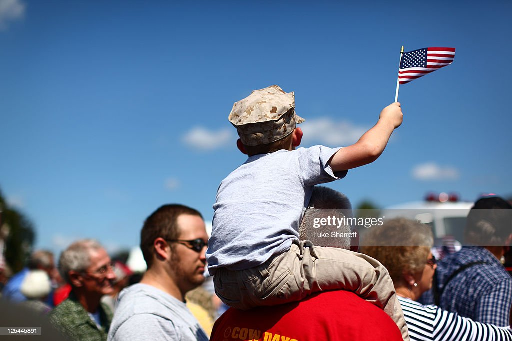 Michael Lewis of Winchester Kentucky waves an American flag during the Cow Days Festival parade in which former active duty Marine Corps Corporal and...