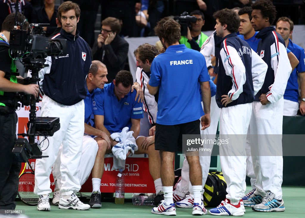 Michael Llodra of France is consoled by captain Guy Forget and french team mates after losing the deciding rubber to Viktor Troicki of Serbia during...