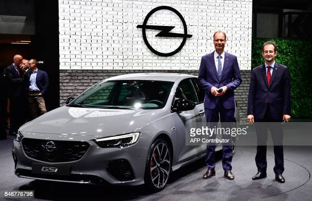 Michael Lohscheller CEO of Opel and Opel's CFO Philippe de Rovira pose next to an Opel car during the official opening of the Internationale...