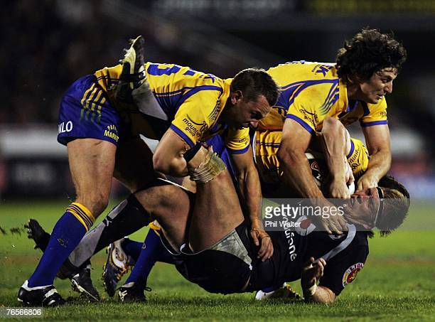Michael Luck of the Warriors is tackled to the ground by Chad Robinson and Nathan Hindmarsh of the Parramatta Eels during the NRL qualifying final...