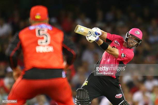 Michael Lumb of the Sixers hits a six as Aaron Finch captain of the Renegades looks during the Big Bash League match between the Melbourne Renegades...