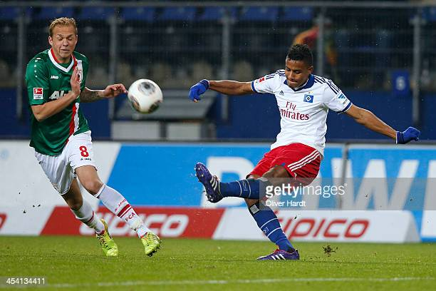 Michael Mancienne of Hamburg and Raphael Holzhauser of Augsburg compete for the ball during the Bundesliga match between Hamburger SV and FC Augsburg...